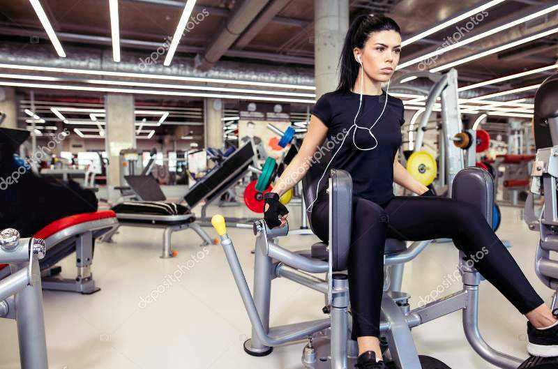Adduction or abductor machine. fit girl exercising her legs in gym (credited depositphoto)