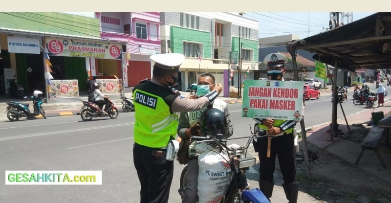 Tampak Anggota Satlantas Polres Oku Selatan Sedang Memasangkan Masker Kepada Salah seorang Pengendara Yang Abai tidak Memakai Masker (Foto Dok Satlantas Polres oku Selatan)